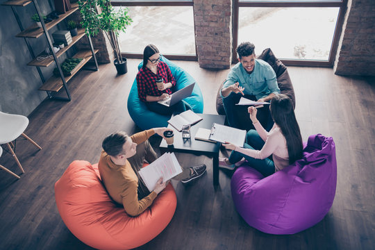 Top above high angle view of nice attractive smart clever interns managers reviewing development attending internship sitting on bag chair at industrial loft interior workplace workstation