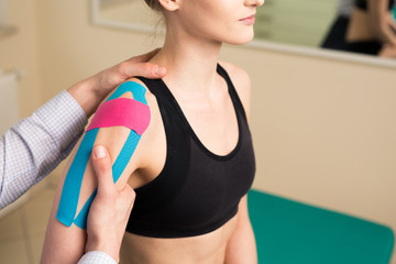 Kinesiotaping. Physical therapist doing shoulder exercises with patient