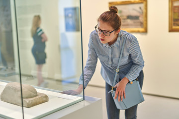 woman visitor historical museum looking at art object