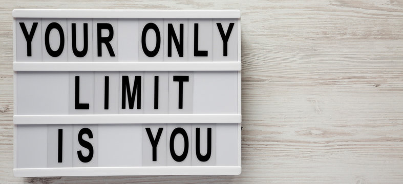 Modern board with 'Your only limit is you' words on a white wooden background, top view. From above, flat lay, overhead. Space for text.
