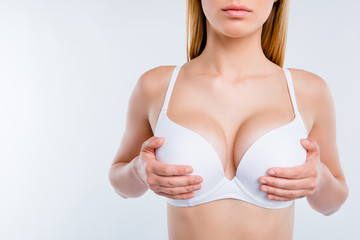 Cropped close-up view of nice gorgeous girl holding in hands perfect big round fit shape chest cancer early diagnostic salon procedure isolated over light gray background