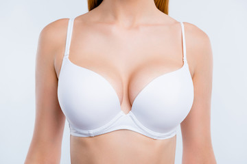 Cropped close-up portrait of nice attractive adorable girl chest after uplift injection wearing white bra isolated over light gray background Wall mural