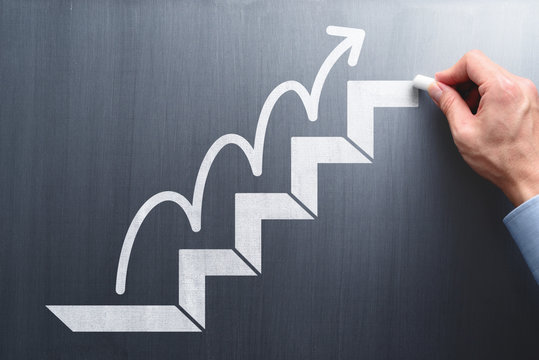 Steps to succeed in business. Businessman drawing steps and arrow on chalkboard.