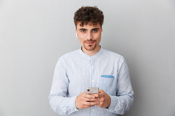 Image of caucasian young man with earpods looking at camera and holding cellphone
