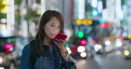 Wall Mural - Woman send voice message on phone in city at night