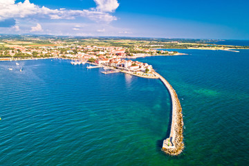 Historic town of Umag and harbor breakwater aerial view