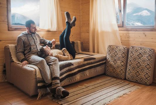 Happy couple have fun on the sofa in cozy winter interior