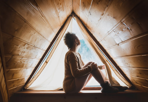 Female silhouette in original designed window. Hipster girl sitting on the window still and looks outdoor alone