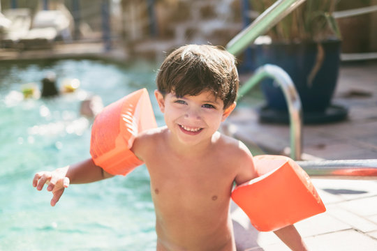 little three years old kid boy with arms float in swimming pool ready to go to water