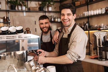 Fototapeta Group of cheerful men baristas wearing aprons obraz