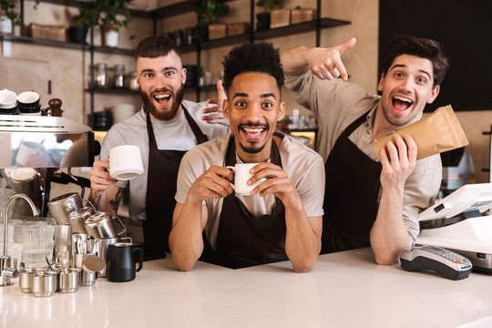 Group of cheerful men baristas wearing aprons
