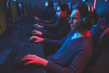 Serious concentrated esports player concentrated on game wearing wired headset sitting at table and playing online multiplayer game