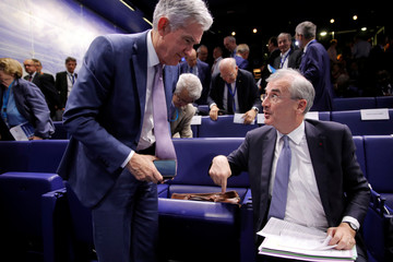 """Governor of the Bank of France Villeroy de Galhau talks with Federal Reserve Board Chairman Powell during a conference entitled """"Bretton Woods: 75 years later"""" in Paris"""