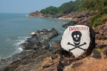 Prohibition sign skull and bones on the dangerous ocean beach