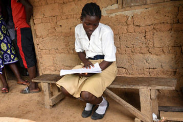 Mariatu Sesay, 15, checks her notes outside her house in a countryside village of Sierra Leone