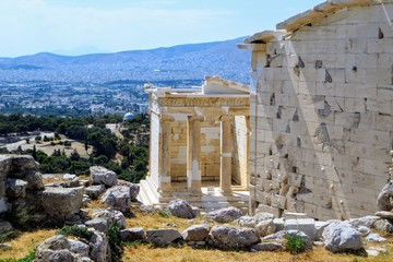 A view of the Temple of Athena Nike , which is a temple on the Acropolis of Athens, dedicated to the goddess Athena Nike.  The city of Athens is in the background