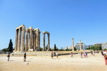 A group of tourists walking around admiring the remains of Temple of Olympian Zeus in Athens, Greece on a beautiful hot summer day.