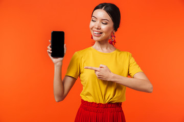 Excited happy young woman posing isolated over orange wall background showing display of mobile phone.