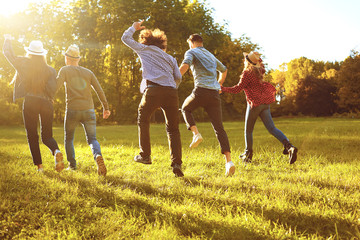 A group of young people running through the park. Wall mural