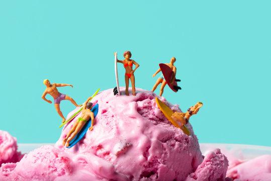 miniature people surfing on an ice cream ball