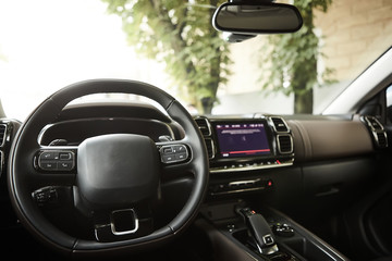 Modern luxury car Interior - steering wheel, shift lever and dashboard. Car interior luxury inside. Steering wheel, dashboard, speedometer, display. Black leather cockpit.