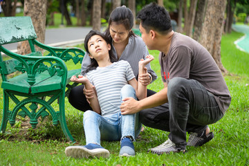 Sick child girl with epileptic seizures at park,daughter suffering from seizures,illness with epilepsy during seizure attack,asian mother,father care of girl patient,brain,nervous system concept
