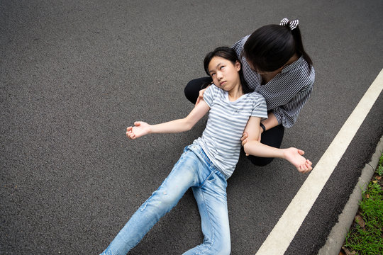 Sick child girl with epileptic seizures on street,daughter suffering from seizures,illness with epilepsy during seizure attack,asian woman or mother care of girl patient,brain,nervous system concept