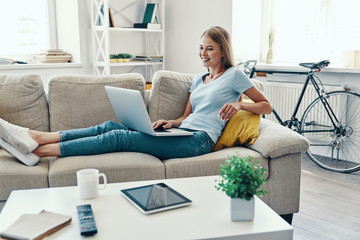 Beautiful young woman smiling and using laptop while resting on the sofa at home