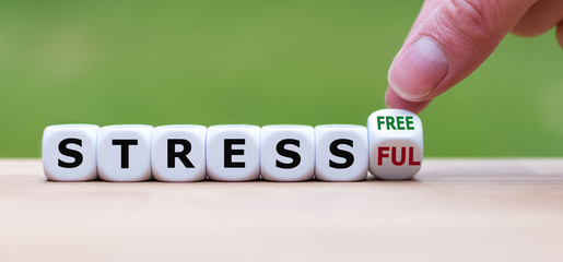 """Hand turns a cube and changes the expression """"stressful"""" to """"stress free""""."""