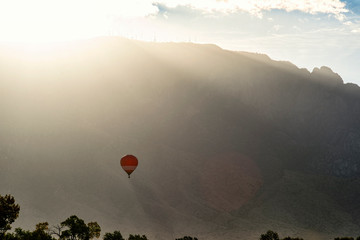hot air balloon flying near mountains at sunrise