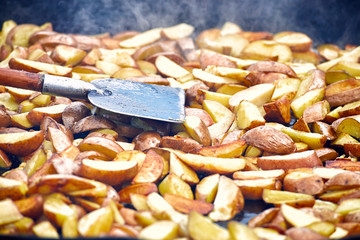 Frying potatoes in a large pan in the countryside.