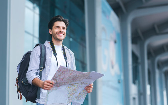 Cheerful man traveler holding map, studying new destinations at airport