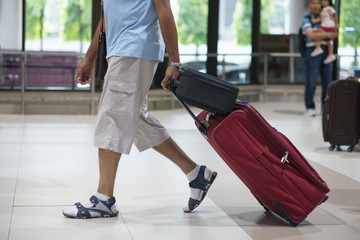 Traveler pulling suitcase in airport terminal.