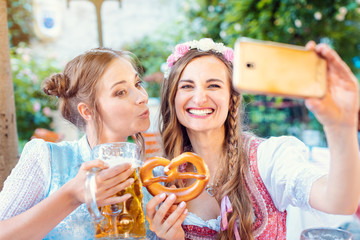 Best friends in Bavarian Tracht making a Selfie with the phone