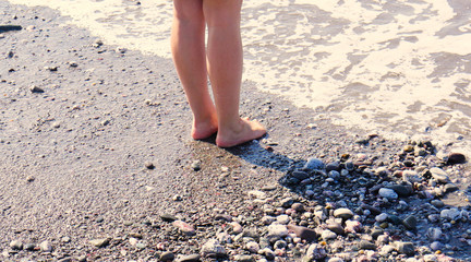 At the edge of the sea, woman's feet/legs with the sea gently lapping them