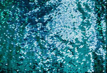 Shiny background made of turquoise sequins. Luxury scaly Background