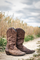 Cowboy boots on dirt road next to wheat field