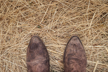 Standing in cowboy boots on hay