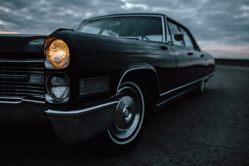 Engels, Russia - June 08, 2018: Black retro vintage muscle car Cadillac Fleetwood Brougham is parked at countryside asphalt road at dusk