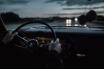 Engels, Russia - June 08, 2018: Black retro vintage muscle car Cadillac Fleetwood Brougham is driving at countryside asphalt road at dusk. View from interior