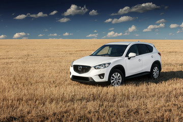 Saratov, Russia - August 30, 2014: White car Mazda CX-5 is parked on yellow grass field at autumn