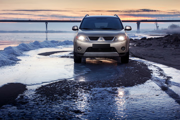 Saratov, Russia - November 27, 2014: Car Mitsubishi Outlander is standing on ice coast at winter sunset