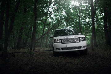 Saratov, Russia - August 08, 2016: White car Land Rover Range Rover is parked in the forest