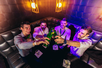 Group of young men toasting at a nightclub Wall mural