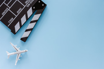 Movie clapper board with white airplane model on blue background