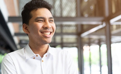 close up young handsome of muslim man smiling and looking forward with happy and confident feeling at outside office for millennial lifestyle and healthy life concept