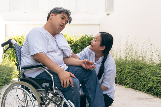 The wife is taking care of the husband sitting on wheelchair,  who is suffering from neurological diseases, or hemiplegia having a facial palsy and kinking fingers, to health and paralysis concept.