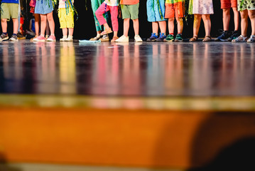 Children on a stage to represent a work in their school, unrecognizable, only their feet with copy space.