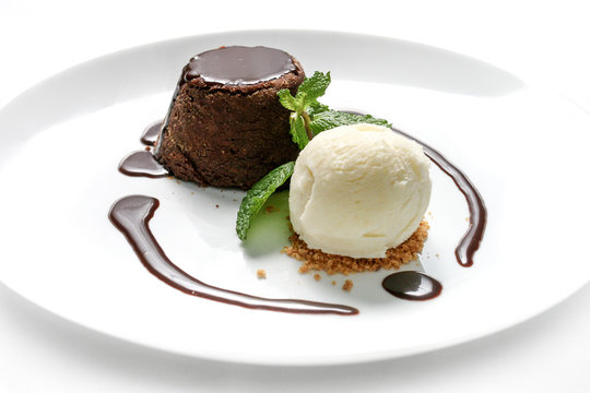 """Delicious """"petit gateau"""" chocolate cake with cacao syrup, vanilla ice cream and mint leaf served on white plate with white background."""