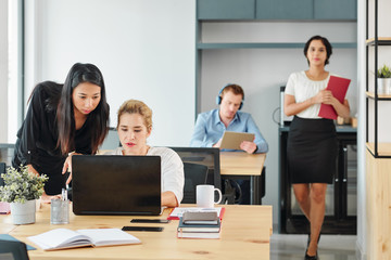 Group of young business people sitting at their workplaces and working with laptop computers with young businesswoman walking along the office corridor
